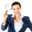 Young attractive business woman looking into a magnifying glass — Stock Photo #31102145