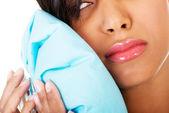 Mujer presionando su mejilla amoratada con una expresión dolorosa — Foto de Stock