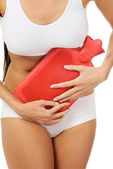 Woman belly with hot water bottle — Stock Photo