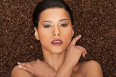 Attractive woman lying in coffee grains. Fron view. Closeup. — Stock Photo