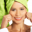 Attractive woman wrapped in towel, holding her mouth in a smile. — Stock Photo #35033077