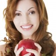 Attractive casual woman holding an apple. — Stock Photo