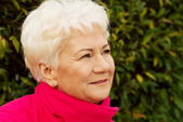Portrait of a cheerful old lady over green background. — Stock Photo