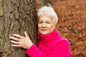 Portrait of an old cherrful lady standing next to a tree. — Stock Photo