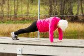 Active grandmum doing push-ups on fresh air. — Stock Photo