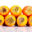 Composition of kaki fruits over white. — Stock Photo