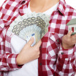Casual woman holding money and house on hands. — Stock Photo