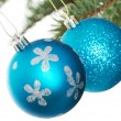 Two blue christmas balls handing on a fir. — Stock Photo