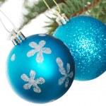 Two blue christmas balls handing on a fir. — Stock Photo