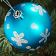 One blue christmas ball handing on a tree. — Photo