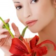 Portrait of beautiful woman with red lily flower. — Stock Photo