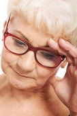 An old woman holding her head, thinking or worrying. — Stock Photo
