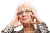 An old woman touching her face, temples. — Stock Photo