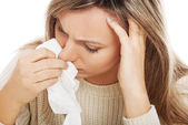 Young woman with tissues crying or having runny nose. — Stock Photo