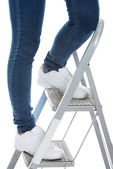 Woman in jeans on a step ladder. — Stock Photo