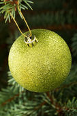 One gold christmas ball hanging on a tree. — Stock Photo