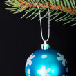 Stock Photo: One christmas ball handing on a twig.