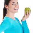 Young casual woman holding an apple. — Stock Photo