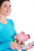 Casual student woman holding workbook and piggy-bank. — Stock Photo