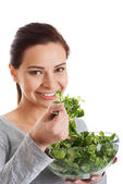 Young casual woman eating lamb's lettuce. — Stock Photo