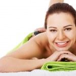 Beautiful woman lying on spa salon having stone massage. — Stock Photo