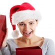 Beautiful woman in santa hat and opening present. — Stock Photo