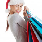 Beautiful woman in santa hat carrying shopping bags. — Stock Photo