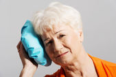An old lady with ice bag by her head. — Stock Photo