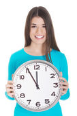 Young casual woman is holding a clock. — Stock Photo