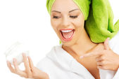 Beautiful woman in bathrobe, turban and holding face cream. — Stock Photo