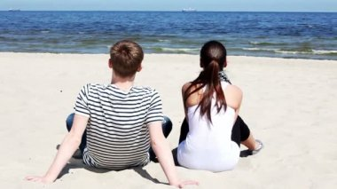 Young couple sitting on sand on beach in casual clothes and looking on waves — Stock Video