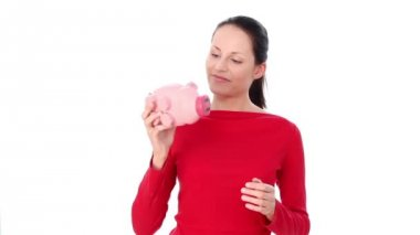 Lovely woman with piggy bank. Over white background. — Stock Video