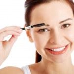 Beautiful young woman with eye brush. — Stock Photo