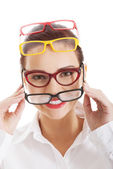 Beautiful woman wearing four different pairs of eyeglasses. — Stock Photo