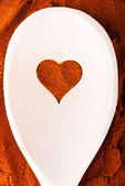 Heart shape made from spice on a wooden spoon. — Stock Photo