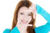 Lachende vrouw dragen blauwe blouse vertoont frame door handen. — Stockfoto