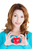 Attractive smiling woman showing red heart — Stock Photo