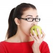 Attractive young woman eating green apple. — Stock Photo