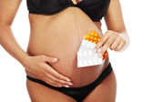Young beautiful pregnant woman holding pills — Stock Photo