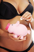 Young beautiful pregnant woman holding a pink piggybank — Stock Photo