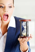 Young business woman with hourglass - time concept — Stock Photo