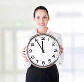 Happy young business woman holding office clock — Stock Photo