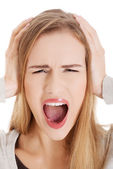 Beautiful casual woman screams and covers her ears. — Stock Photo