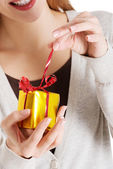 Beautiful woman unwrapping small present. — Stock Photo