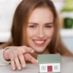 Beautiful caucasian woman and small house model. — Stock Photo