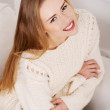 Beautiful woman in bright sweater sitting on a couch. — Stock Photo #39140633