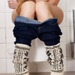 Stock Photo: Young caucasiwomis sitting on toilet.