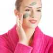 Beautiful caucasian woman in pink bathrobe is having facial mask — Stock Photo