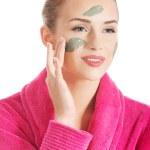 Beautiful caucasian woman in pink bathrobe is having facial mask — Stock Photo #39142149