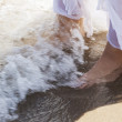 Pictore of feet on a beach and water. — Stock Photo